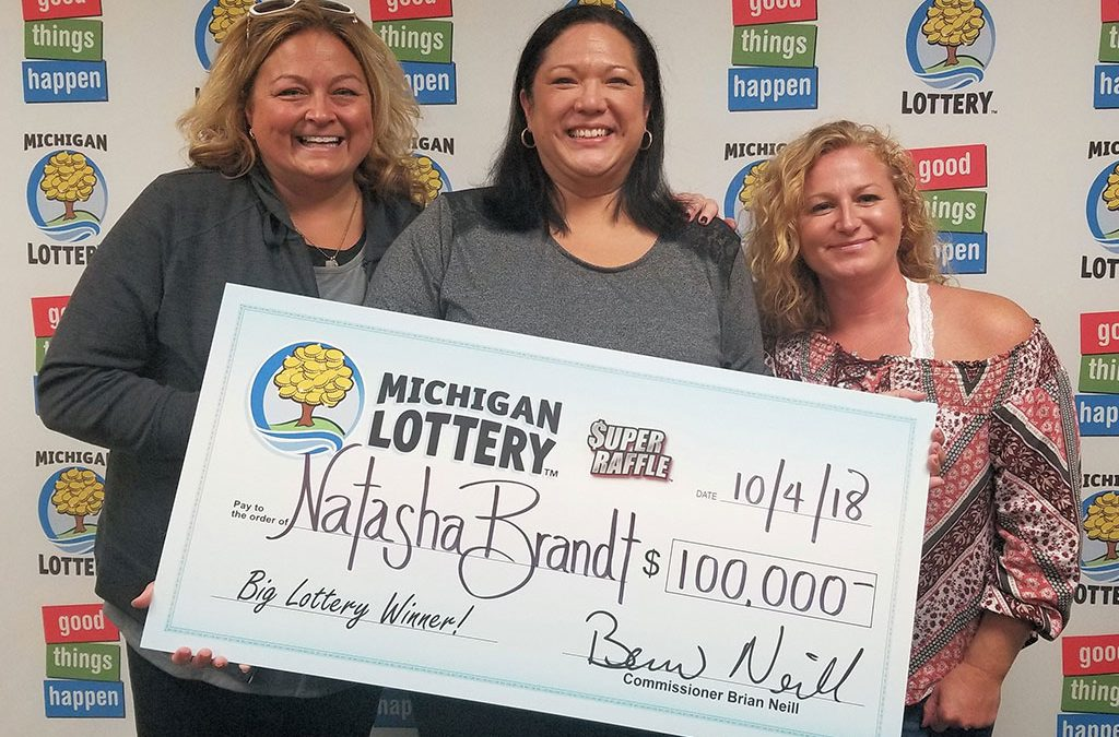 Natasha Brandt (center) smiles after collecting her $100,000 prize with friends Kelley White (left) and Brenna Lantz (right)